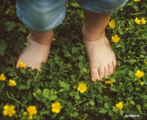 Feet of toddler among flowers