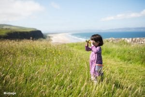 toddler girl playing exploration at sunny summer countryside, Northern Ireland