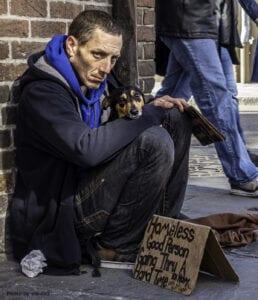 A homeless man squatting on the street