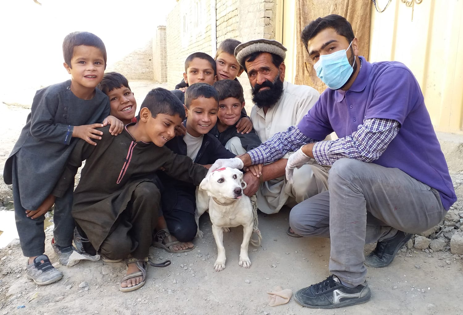 Mayhew Afghanistan driver with adopted street dog and its fans!