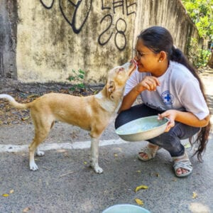 BCI volunteer feeding a street dog