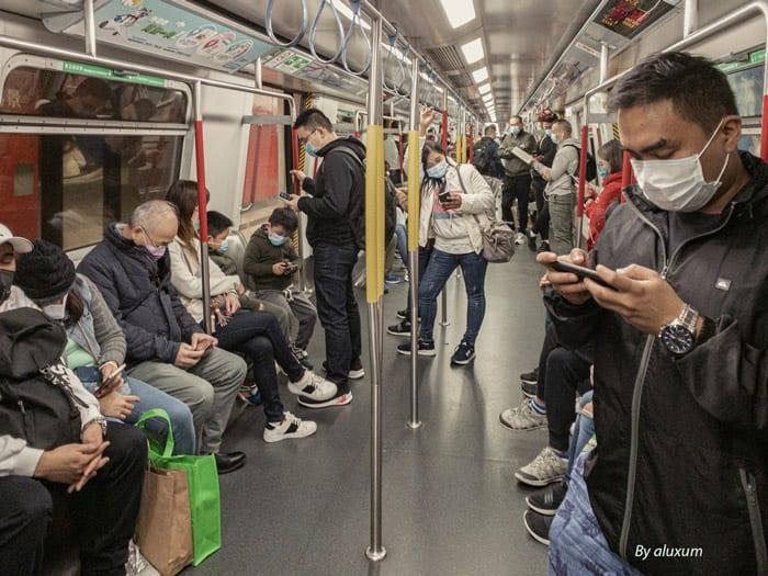 Hong Kong subway passengers with mobile phones